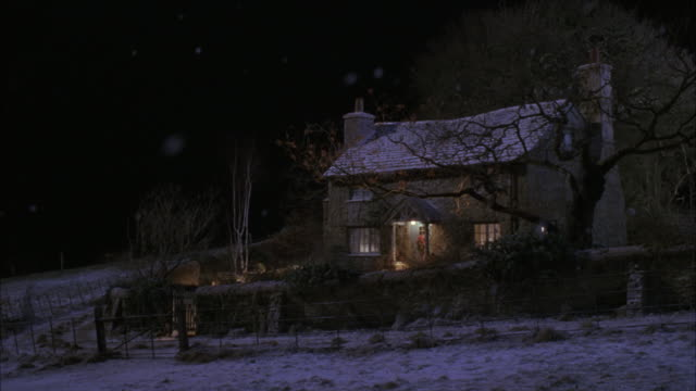 wide angle of quaint cottage or house with wreath on door, smoke coming from chimney, snow falling. winter, christmas. rural areas. - wreath stock videos & royalty-free footage