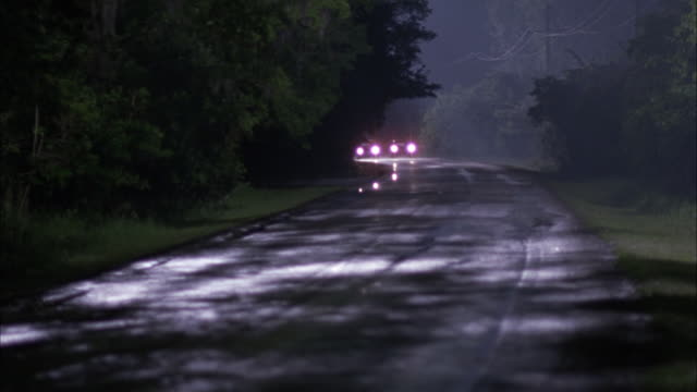 wide angle of vintage cars driving on rural area two lane road. headlights shine. one car passes second car, near collision with third car traveling in opposite direction. - vintage car stock videos and b-roll footage