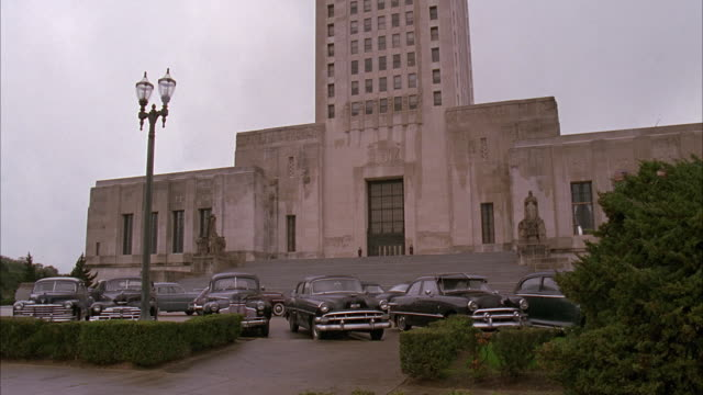 PAN UP OF LOUISIANA STATE CAPITOL BUILDING. GOVERNMENT BUILDINGS, STATUES, LARGE STONE STAIRCASE. SEVERAL CLASSIC CARS IN PARKING LOT.  HEDGE. ART DECO ARCHITECTURAL STYLE.