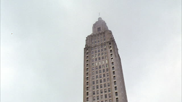wide angle of louisiana state capitol building, partially obscured by clouds. government building, overcast sky. art deco architectural style. - kapitol von louisiana stock-videos und b-roll-filmmaterial