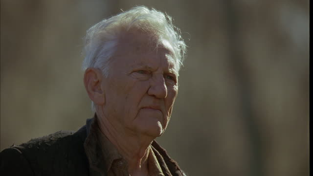 CLOSE ANGLE OF ELDERLY MAN, FROWNING AND STARING OFFSCREEN.