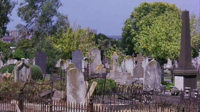 MEDIUM ANGLE OF MELBOURNE GENERAL CEMETERY. GRAVEYARD CONTAINS VICTORIAN ERA HEADSTONES AND GRAVES ENCLOSED IN RUSTING WROUGHT IRON FENCES. OBELISKS AND CROSSES ADORN SEVERAL TOMBSTONES.