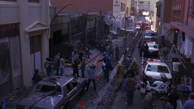 HIGH ANGLE DOWN SHOWING STREET SCENE AFTER DISASTER, EXPLOSION, OR FIRE WITH FIREMEN, NEWS CREWS AND REPORTERS, POLICEMEN, AND POLICE CARS. CONSTRUCTION WORKERS CLEAR RUBBLE FROM BURNED OUT STOREFRONTS.