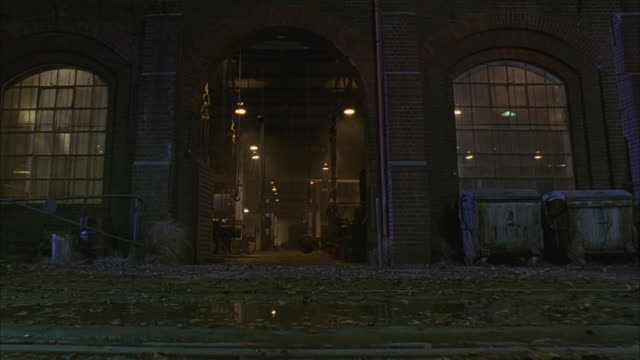 MEDIUM ANGLE OF WAREHOUSE. TRAIN TRACKS, LEAVES, PUDDLES ON GROUND. WINDOWS WITH CURTAINS ON SIDE OF ENTRANCE. CAMERA MOVES INTO DOORWAY. LIGHT FIXTURES AND CHAINS HANG FROM SCAFFOLDING. COULD BE ABANDONED WAREHOUSE, INDUSTRIAL BUILDING.