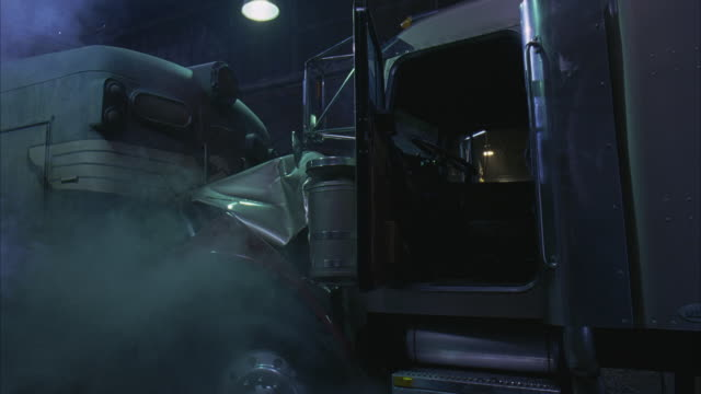 MEDIUM ANGLE OF SEMI-TRUCK OR EIGHTEEN WHEELER CRASHED INTO ABANDONED TRAIN CARS AFTER ACCIDENT OR COLLISION. TRUCK DOOR OPEN SHOWING EMPTY CAB OF TRUCK. SMOKE POURS FROM ENGINE. STUNTS.