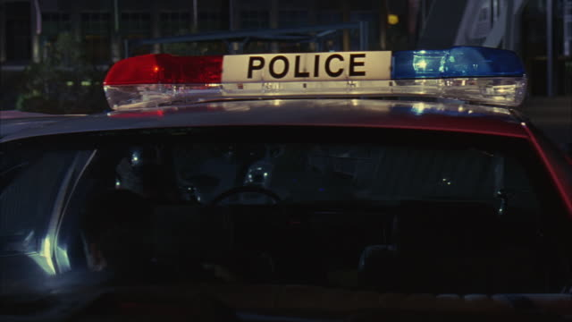 medium angle of police car from the rear, police officers sitting inside under the lit bizbar. police officers jump out of the car and rush onto the trinity pedestrian bridge with other police. - gewehr stock-videos und b-roll-filmmaterial