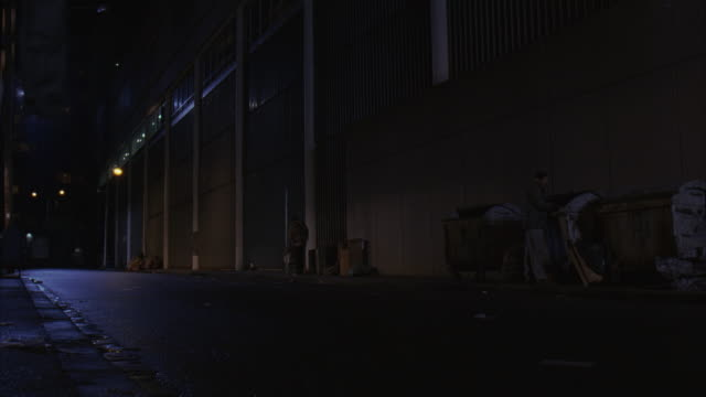 wide angle of alley in urban area, multi-story buildings. homeless men, dumpsters, trash. - housing difficulties stock videos & royalty-free footage