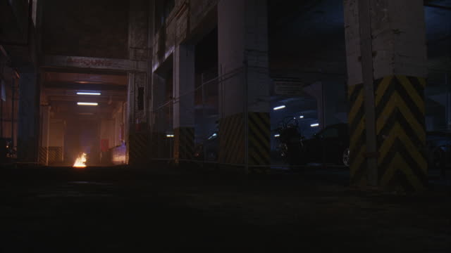 WIDE ANGLE OF IMPOUND, PARKING GARAGE WITH FIRE, FLAMES BURNING IN CORRIDOR. GARAGE HAS CHAIN LINK FENCE, CARS, MOTORCYCLE AND CEMENT COLUMNS. 48 FPS.