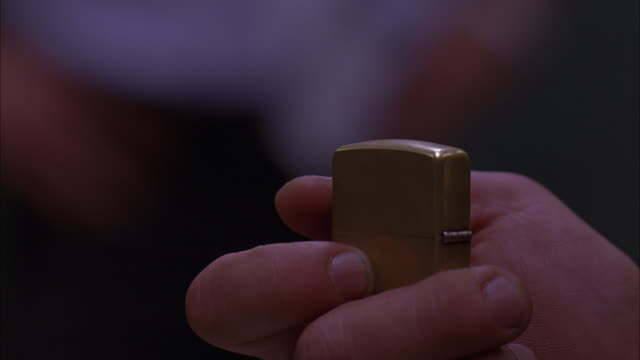 CLOSE ANGLE OF HAND HOLDING BRASS CIGARETTE LIGHTER.  MAN IN WHITE TEE SHIRT OUT OF FOCUS IN BACKGROUND.
