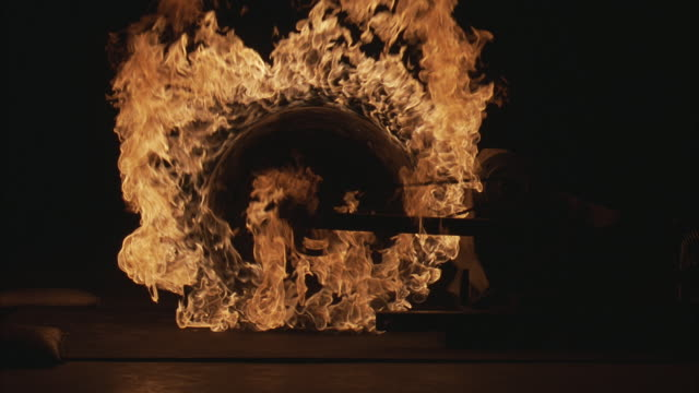 medium angle of flaming motorcycle wheel spinning, being ignited.  fire, flames spin.  for fx compositing. - reifen stock-videos und b-roll-filmmaterial
