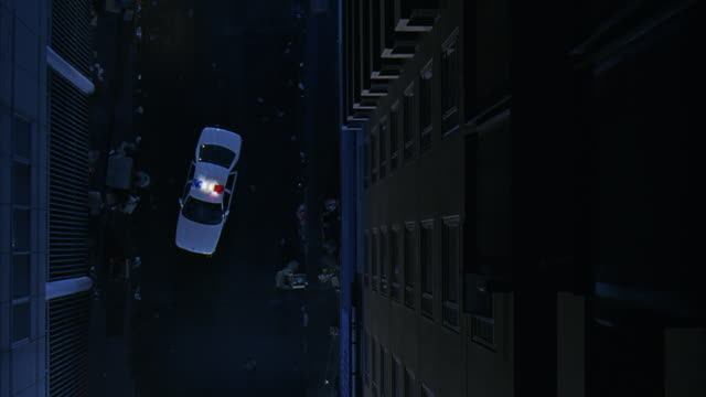 high angle down, birdseye pov, of  police car with bizbars, sirens and flashing lights parked in urban area alley with trash, debris. police officer steps from car. - alley stock videos & royalty-free footage
