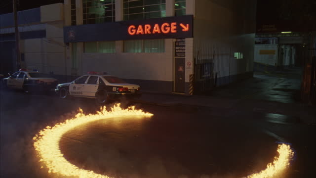 """WIDE ANGLE OF PARKING GARAGE WITH SHERIFF'S POLICE CARS OUT FRONT. RING OF FIRE SLOWLY FORMS IN FRONT, FLAMES FLICKERING AND EMITTING SMOKE THEN NEARLY BURNING OUT. NEON """"GARAGE"""" SIGN WITH ARROW, DRIVEWAY AND RAMP VISIBLE. COULD BE POLICE IMPOUND."""