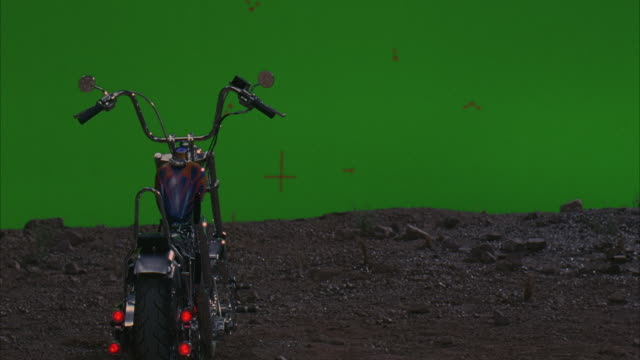 medium angle of chopper motorcycle on dirt debris strewn road in front of green screen. motorcycle has blue paint with flame details. - dirt track stock videos & royalty-free footage