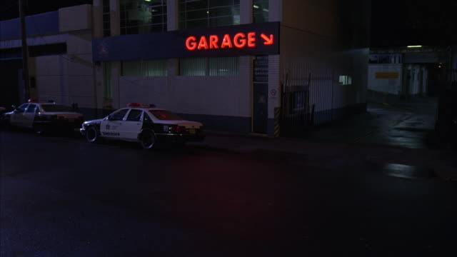 """WIDE ANGLE OF PARKING GARAGE, LOT WITH SHERIFF'S POLICE CARS OUT FRONT. DRIVEWAY INTO GARAGE, RAMPS, GATE AND NEON SIGN """"GARAGE"""" WITH ARROW SEEN. COULD BE POLICE IMPOUND."""