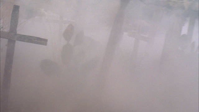 hand held shows crude wood crosses or headstones and graves in foggy cemetery. graveyard is old and neglected. headstones. tombstones. could be used for halloween, old west. - friedhof stock-videos und b-roll-filmmaterial