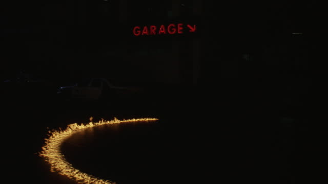 """WIDE ANGLE OF PARKING GARAGE WITH SHERIFF'S POLICE CARS OUT FRONT. RING OF FIRE SLOWLY FORMS IN FRONT, FLAMES FLICKERING AND EMITTING SMOKE THEN NEARLY BURNING OUT. NEON """"GARAGE"""" SIGN WITH ARROW VISIBLE. COULD BE POLICE IMPOUND."""