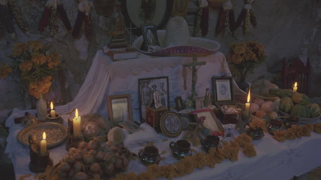medium angle of catholic altar with religious statues or jesus christ and the virgin mary, candles, photographs, crosses, a sombrero and flowers. - 宗教上のシンボル点の映像素材/bロール