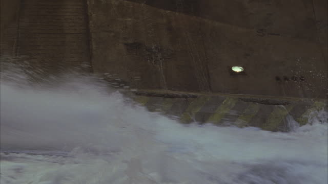 vídeos de stock, filmes e b-roll de medium angle of sewer, drainage facility or water plant, water sliding down slanted walls. flood of water rushes through. - water plant
