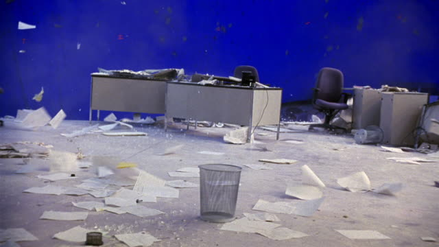 vidéos et rushes de medium angle of office building with damage to outer perimeter. floor collapses, desks, chairs, papers go sliding, falling off the edge. disasters. - se déplacer vers le bas