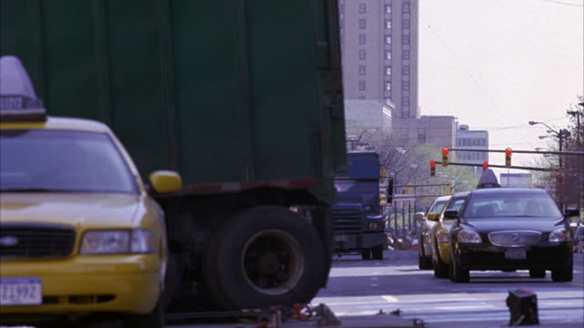 wide angle of blue armored car driving towards pov crash into dump truck on new york city street, truck flies into air briefly then turns to show hole in side. taxis, parked cars seen on street. collisions. accidents. car stunts. 60 fps. - dump truck stock videos and b-roll footage