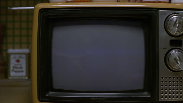 PULL BACK FROM CLOSE ANGLE OF BLANK TELEVISION SCREEN TO WIDE ANGLE OF VINTAGE TELEVISION SET ON  KITCHEN COUNTER