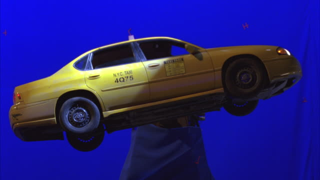 "close angle of model of ""nyc taxi"" in front of blue screen suspended by pole. car shakes violently then tips forward, backward as flashlights or search lights shine on body of car and in window. - taxi video stock e b–roll"