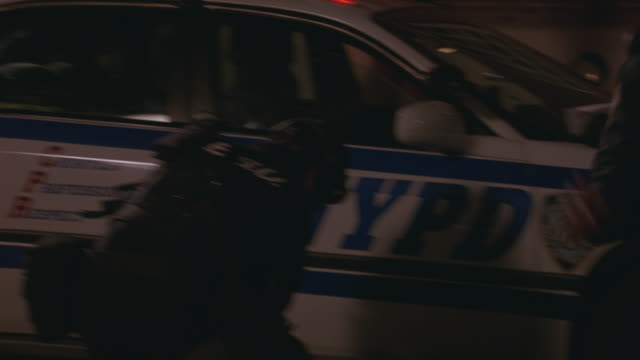 MEDIUM ANGLE POLICE PUSHING BACK A BUSY CROWD AT A NEW YORK INTERSECTION.  THE CROWD LOOKS PAST THE POLICE LINE AS FIREFIGHTERS RACE BY AND THE SWAT TEAM SETS UP NEXT TO A POLICE CAR.