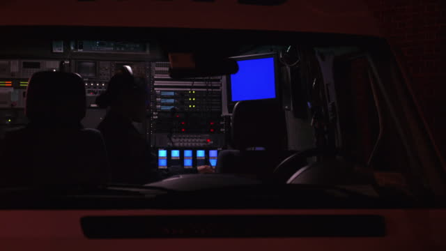 MEDIUM ANGLE OF POLICE SURVEILLANCE VAN.  COPS AND FIREFIGHTERS WALK OUTSIDE THE VAN AS A POLICE OFFICER INSIDE MONITORS THE VIDEO SURVEILLANCE EQUIPMENT.