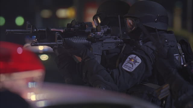 medium angle of swat police officers behind police cars aiming semiautomatic machine guns, weapons. cops fire guns then react as if explosion has occurred. - waffe stock-videos und b-roll-filmmaterial
