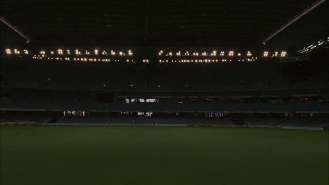 "wide angle of south ""coventry"" side of melbourne's telstra dome stadium. sports arena has field, advertisement banners, electronic scoreboard, lights and bleachers. retractable roof is closed. - sports equipment stock videos & royalty-free footage"