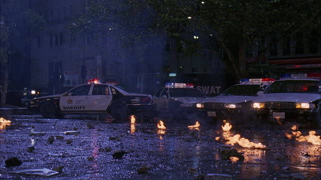 stockvideo's en b-roll-footage met medium angle of police cars and swat truck stopped in front of flaming rubble, debris. bizbar lights are flashing on sheriff's cars. fire could be from explosion. office buildings in background. - 2007