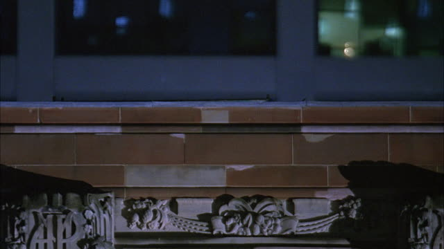 close angle of brick wall and crumbling marble decorations on rooftop of building. office building visible in background. - marble wall stock videos and b-roll footage