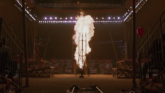 vídeos de stock e filmes b-roll de wide angle of stunt at circus or stadium. hoop ignites into flames. two motorcycles jump through flaming hoop off ramps. crowds of spectators can be seen in surrounding stands. - circo