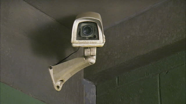close angle of surveillance or security camera in corner near ceiling of brick room with grey and green paint. could be jail or prison. - surveillance camera stock videos & royalty-free footage