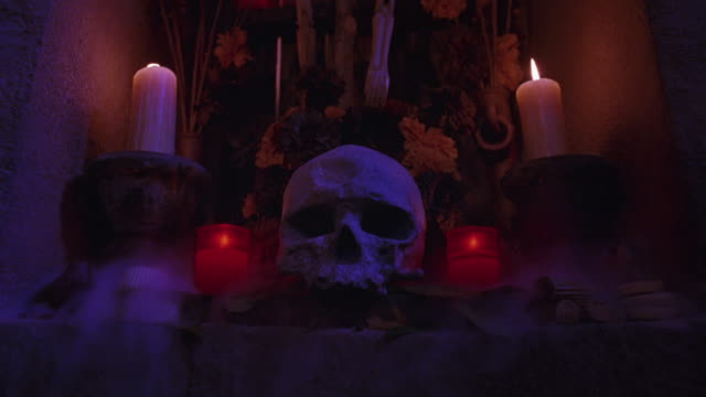 MEDIUM SHOT OF SKULL, CANDLES AND DRIED FLOWERS ON RELIGIOUS OR DAY OF THE DEAD ALTAR. FOG ROLLS OFF ALTAR OR SHRINE.
