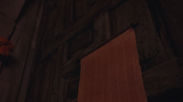 close angle of scroll or paper nailed to wood door of stone building, possibly church or  mission. gloved hand tears scroll off door. paper has list of names written in red ink or blood. 48 fps. - paper scroll stock videos and b-roll footage