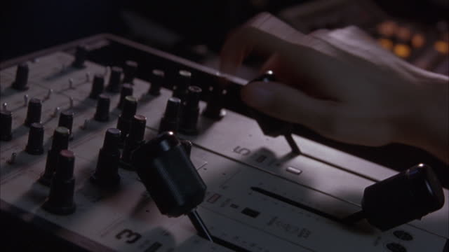 close angle of control panel in television station or studio. hand pushes levers up and down, turns knobs on console. - lever stock videos & royalty-free footage