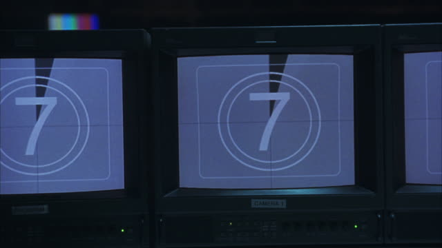 pan left to right along television monitors displaying countdown, stop on close angle of one monitor. monitors are on control panel - 2005 stock videos & royalty-free footage