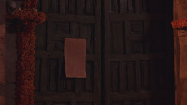 zoom in from medium angle of doorway, entrance of church or mission decorated with flower garlands and skulls to scroll, paper nailed to carved wooden door. - paper scroll stock videos and b-roll footage
