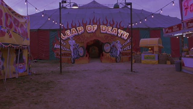 "zoom into carnival or fair tent with pictures of stunt motorcycles on it and text reading ""leap of death."" popcorn vendors and other carnival tents can be seen. camera zooms into tent, showing entrance way with cut out flames and spotlights. - popcorn stock videos & royalty-free footage"