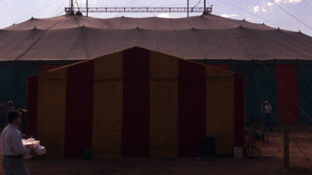 zoom in from wide angle of striped circus tent to close angle of tent entrance, flaps. people, workers seen outside tent - festzelt stock-videos und b-roll-filmmaterial