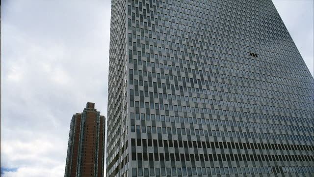wide angle of new york city office buildings. camera sinks below skyscrapers into a park. javits federal office building. foley square. federal plaza. civic centers. spidey-cam. - federal building stock videos and b-roll footage