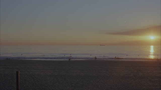 wide angle of sandy beach at sunset. surfers and swimmers are in water in distance. two surfers carrying surfboards walk towards the water. could be used for santa monica, orange county, southern california beach. pacific coast. - pacific coast stock videos & royalty-free footage