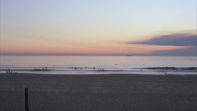 wide angle shot of sandy beach at dusk. surfers and swimmers are in the water, catching waves. a boat can be seen off  in the distance. could be used for santa monica, orange county, southern california beach. pacific coast. - pacific coast stock videos & royalty-free footage