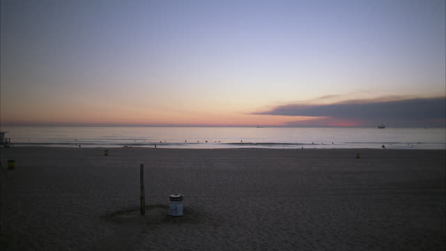 wide angle shot of sandy beach at dusk. in the distance surfers and swimmers in the water. boat in the far distance. a man wearing shorts walks across foreground. - pacific coast stock videos & royalty-free footage