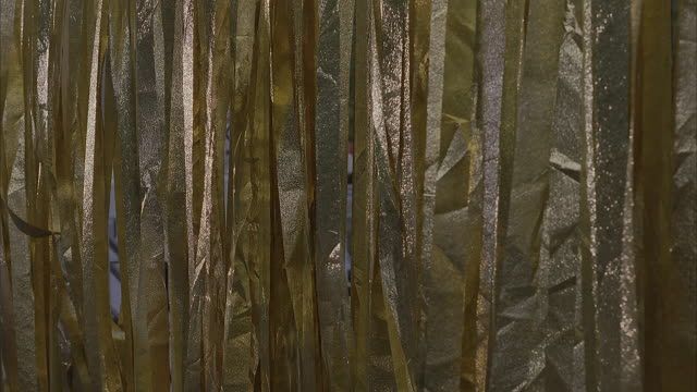 medium angle of gold fabric curtains, ribbons, or streamers. curtains slowly move in the breeze, catching the light. could be used as background for a stage. - streamer stock videos & royalty-free footage