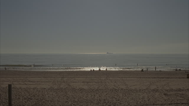 wide angle of sunny, sandy beach. water with swimmers and surfers in it is seen in background. people are seen walking and sitting on beach. could be used for santa monica, orange county, southern california beach. pacific coast. - pacific coast stock videos & royalty-free footage