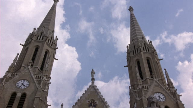 """pan down from twin spires to  ground floor entrances of saint erzsebet church. statue of woman in front reads """"szent erzsebet,"""" otherwise known as saint elizabeth of hungary. - spire stock videos & royalty-free footage"""