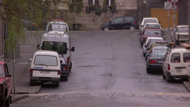 medium angle of a military convoy of green russian trucks and jeeps through a quiet residential area, probably budapest. - ungarn stock-videos und b-roll-filmmaterial