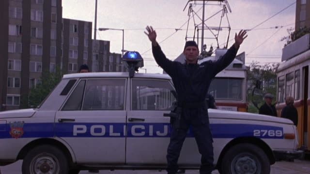 vidéos et rushes de medium angle of a police officer standing in front of his car at a check point on railroad tracks. several pedestrians getting on the trams behind the car. the camera pushes into the side of the car and officer jumps out of the way. - hongrie